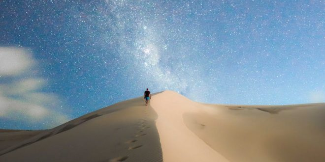 photo of person walking on desert during evening
