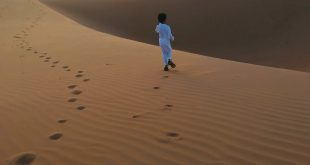 back view photo of muslim boy in white thobe walking alone on desert sand during golden hour