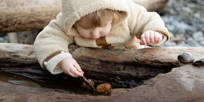 cute little girl playing with stones on log on shore