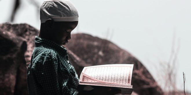 photo of boy holding book