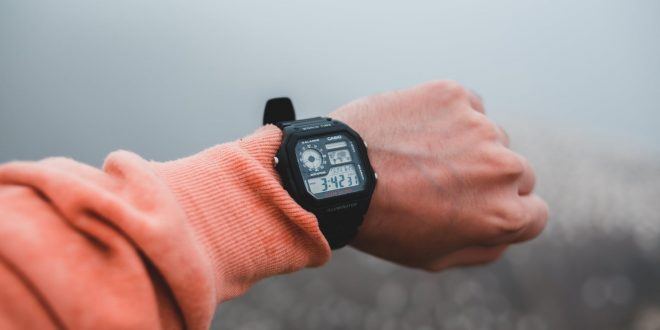 crop man showing modern wristwatch with display on foggy day