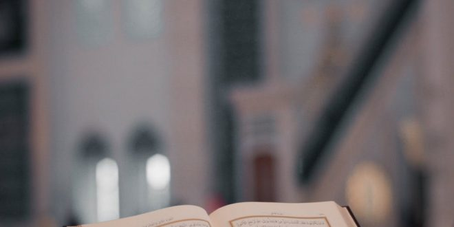 opened religious book on stone desk in mosque backyard
