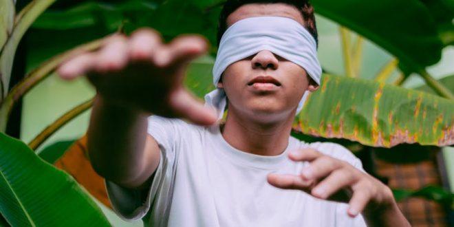 man wearing white blindfold