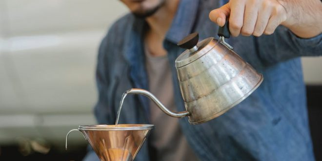 positive young ethnic guy pouring water into cup while preparing coffee